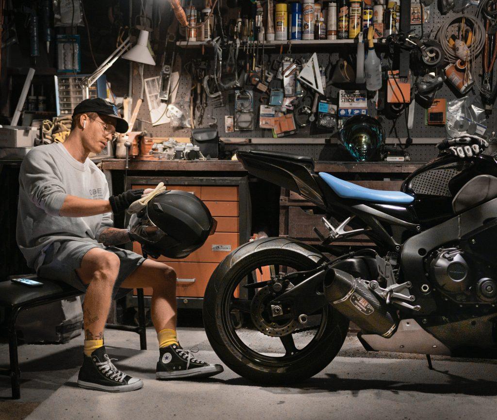 uomo che pulisce casco con moto
